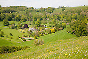 Steep chalk escarpment  looking into deep green valley containing Rainscombe House, Vale of Pewsey, near Oare, Wiltshire, England, UK