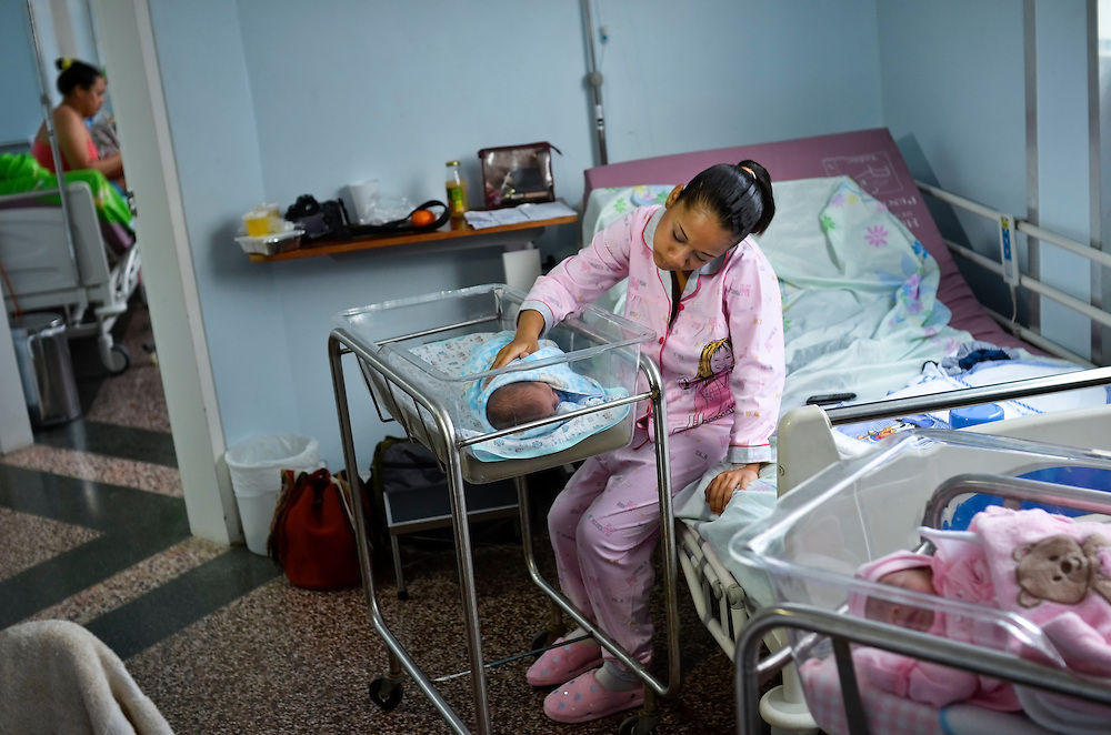 15-year-old, Yanaifre Acevedo, dressed in Disney's Hannah Montana pajamas, pats her baby Dilan's back at a free, government-run maternity clinic in Caracas, Venezuela.  Acevedo, who wants to be a professional dancer, said she got pregnant by accident, but that she has a secret plan to have her aunt watch her baby so that she can go back to school. She also plans to get a job so that she and her boyfriend can move into their own apartment together. She says her boyfriend is excited to be a father, but he has hardly visited her and their newborn baby.