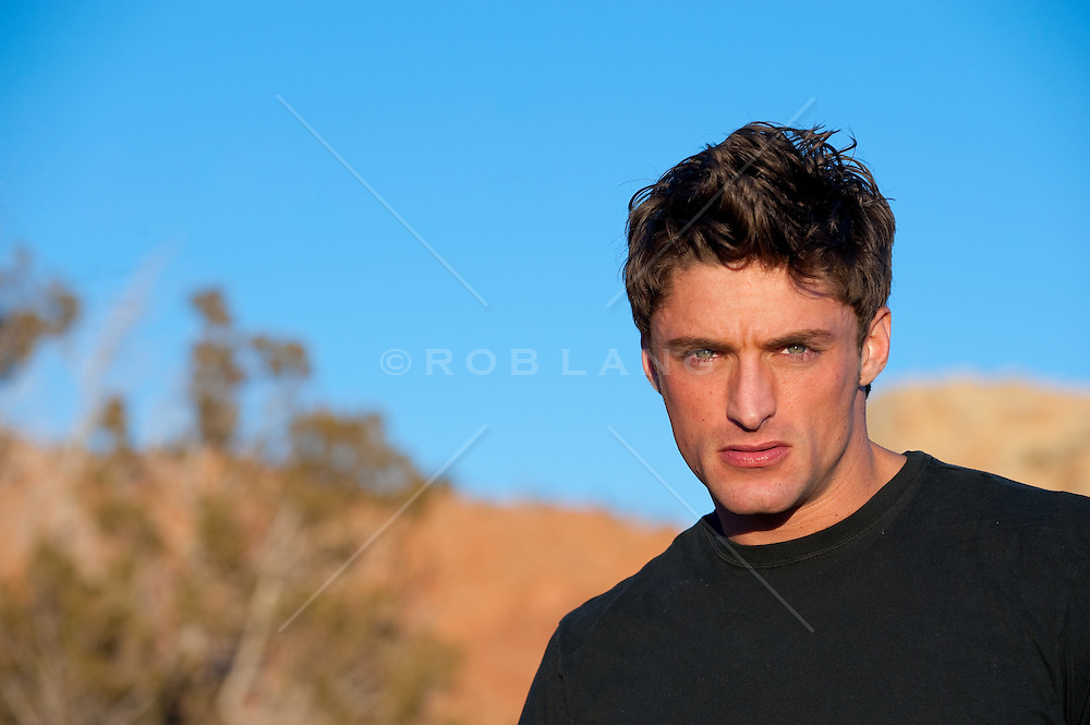 Young man in a black t-shirt, outside in sunlight