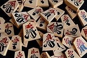 "A set of ""kaki-goma"" (characters painted on with lacquer) shogi playing pieces. Nakajima Seikichi Shoten, Tendo, Yamagata Prefecture, Japan, February 19, 2018. The city of Tendo in Yamagata Prefecture is famous for its shogi (Japanese chess) playing pieces. Production started early in the 19th century and Tendo still produces over 95% of the Shogi pieces made in Japan."