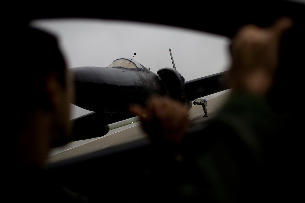 """U2 pilot and chase car driver Captain Eugene Georgescu, left, drives around a U2 before a """"high-flight"""" at Beale Air Force Base February 24, 2010 in Linda, Calif."""