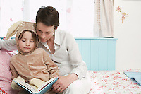 Mother and daughter (5-6) in bedroom reading book girl in bunny costume