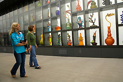Woman gaze at Venetian Wall, glass art by Dale Chihully on Chilhuly Bridge of Glass near Museum of Glass, Tacoma, Washington, USA