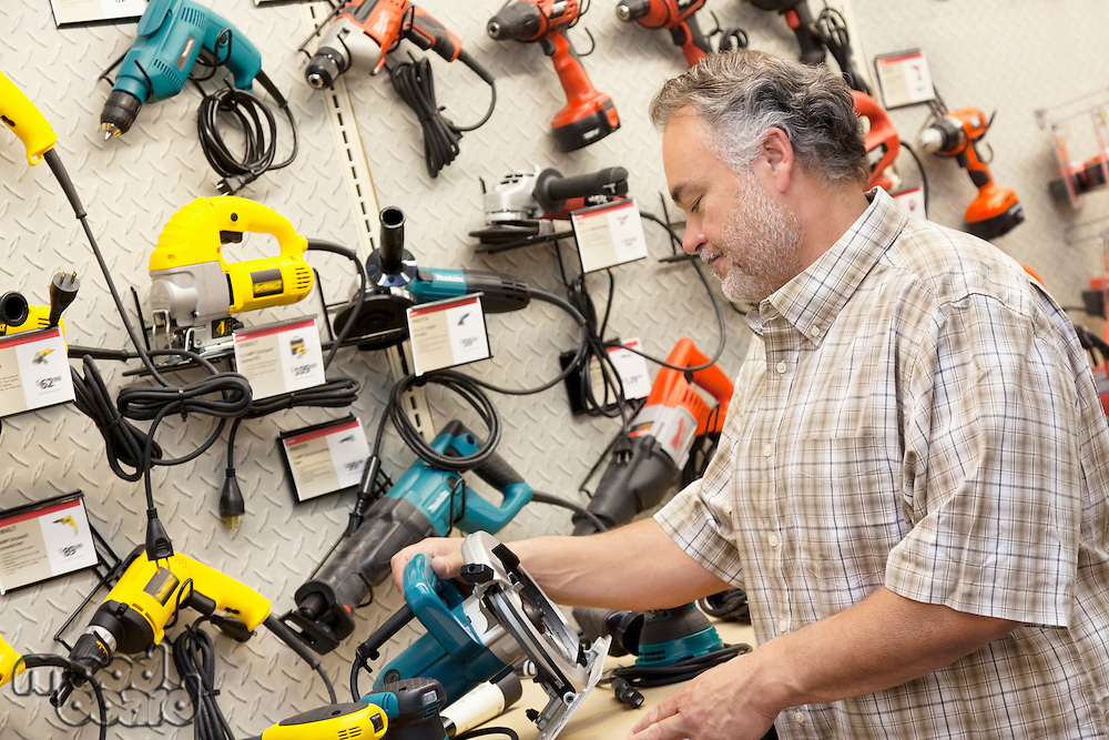 Side view of mature salesperson looking at electric saw
