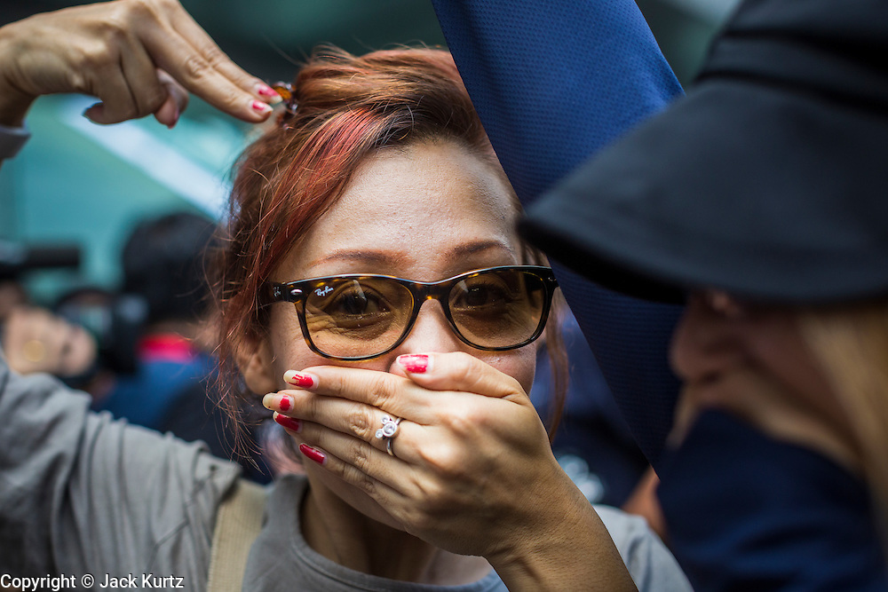 "01 JUNE 2014 - BANGKOK, THAILAND: Thais protest the loss of free speech by covering their mouths and putting their hands shaped as guns to their head during a protest against the coup in Bangkok. The Thai army seized power in a coup that unseated a democratically elected government on May 22. Since then there have been sporadic protests against the coup. The protests Sunday were the largest in several days and seemed to be spontaneous ""flash mobs"" that appeared at shopping centers in Bangkok and then broke up when soldiers arrived. Protest against the coup is illegal and the junta has threatened to arrest anyone who protests the coup. There was a massive security operation in Bangkok Sunday that shut down several shopping areas to prevent the protests but protestors went to malls that had no military presence.    PHOTO BY JACK KURTZ"