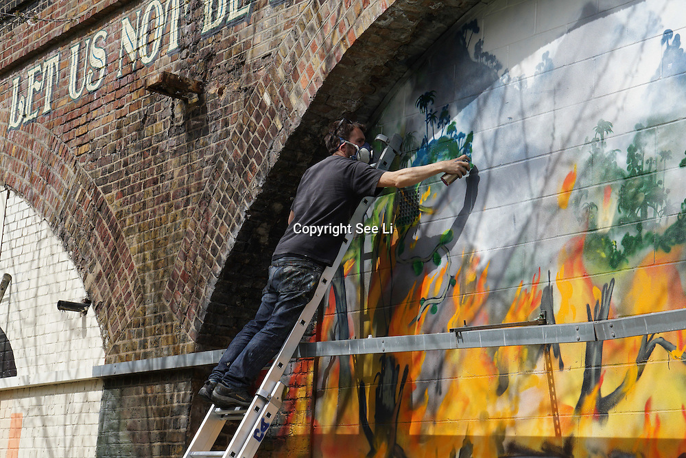 London,England,UK : 10th April 2016 : Graeme brusby. Aka xenz street artists paint a live hummingbirds take on 120 metre stretch of railway arches of 'Endangered 13' at Ackroyd Drive Sponsor by Tower Hamlets council in London. Photo by See Li