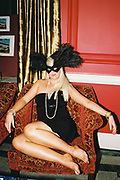 Barefooted woman sitting on a chair wearing black feathered masquerade mask, Posh at Addington Palace, UK, August, 2004