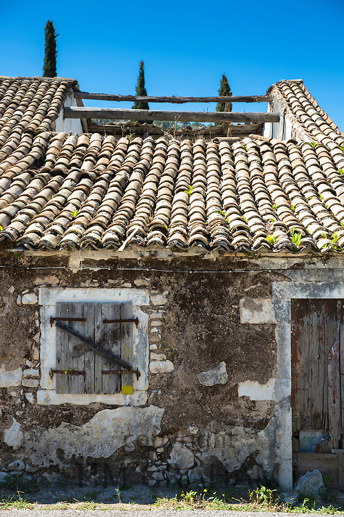 Old shabby derelict house with collapsed roof tiles and shutters in village of Perithia, Northern Corfu, , Greece