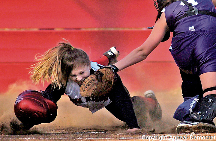 East Nicolaus High's Kaitlyn Cumbie, left, is tagged at home plate by Portola High's catcher Daijia Thomas  on Wednesday at East Nicolaus. The Spartans beat the Tigers 8-1.
