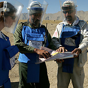 Project manager Rachel Brock (left), 24 from Edinburgh gets a briefing from a local clearance team. Afghanistan remains one of the most heavily mined countries in the world. A mine clearance team from the Halo Trust have been working for more than a year in the small village of Kohe Safi and have removed 800 mines and 118 unexploded bombs. Kohe Safi, Afghanistan on the 1st of November 2007..Throughout the country the Halo Trust alone is working to clear 90 million square meters of mine fields containing some 640,000 mines, they estimate it will take them 18 years to complete this task..A break through in mine detection not seen since  World War II is due to speed things up in the coming year when Halo become the first civillian organisation to use H-STAMIDS (The Handheld Stand-Off Mine Detection System) a new combination tool with a metal detector and ground penetrating radar system. The H-STAMIDS remain classified and during recent trails in Afghanistan the device had to be returned to the US military at the end of each day. The new equipment should make mine clearance 2-3 times faster.
