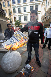 © Licensed to London News Pictures . 06/10/2013 . Manchester , UK . A man sets fire to a copy of The Mail during the protest . A demonstration against the Daily Mail newspaper in central Manchester's St Anne's Square today (6th October 2013) . Photo credit : Joel Goodman/LNP