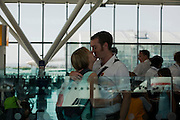Honeymooners kiss before their round-the-world adventure departing from Heathrow Airport's Terminal 5B