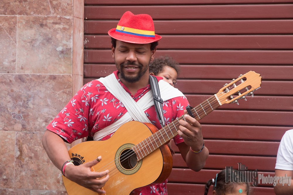 Street musician with child playing music in Quito, Ecuador