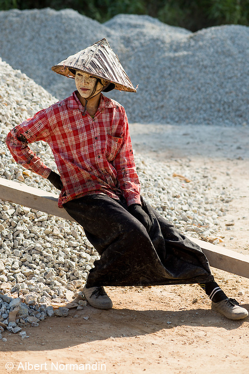 Young girl rests from hard labour road construction work, Myiek