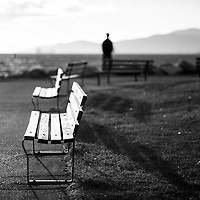 One blurrred silhouetted man standing standing staring into the ocean, another on a bench.