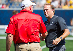 Sep 10, 2016; Morgantown, WV, USA; West Virginia Mountaineers head coach Dana Holgorsen speaks with Youngstown State Penguins head coach Bo Pelini before their game at Milan Puskar Stadium. Mandatory Credit: Ben Queen-USA TODAY Sports