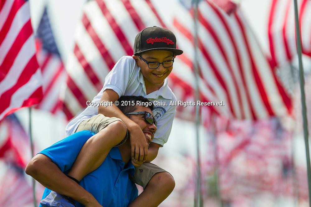 9月10日,在美国加利福尼亚州洛杉矶的马里布,一名父亲背着他的儿子。当天,在美国&ldquo;9&middot;11&rdquo;事件十四周年前夕,佩珀代因大学的学生和教职员工在学校草坪上插起约3000面美国国旗,纪念&ldquo;9&middot;11&rdquo;事件遇难者。新华社发(赵汉荣摄)<br /> A man carries his son amongst 3,000 US flags are displayed at Pepperdine University to mark the 14th anniversary of the 9/11 terror attack, September 10, 2015 in Los Angeles, California, the United States. (Xinhua/Zhao Hanrong)Photo by Ringo Chiu/PHOTOFORMULA.com)
