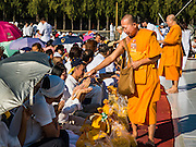 "02 JANUARY 2016 - KHLONG LUANG, PATHUM THANI, THAILAND:  A Buddhist monk passes out amulets before the pilgrimage at Wat Phra Dhammakaya on the first day of the 5th annual Dhammachai Dhutanaga (a dhutanga is a ""wandering"" and translated as pilgrimage). More than 1,300 monks are participating pilgrimage through central Thailand. The purpose of the pilgrimage is to pay homage to the Buddha, preserve Buddhist culture, welcome the new year, and ""develop virtuous Buddhist youth leaders."" Wat Phra Dhammakaya is the largest Buddhist temple in Thailand and the center of the Dhammakaya movement, a Buddhist sect founded in the 1970s. The monks are using busses on some parts of the pilgrimage this year after complaints about traffic jams caused by the monks walking along main highways.         PHOTO BY JACK KURTZ"