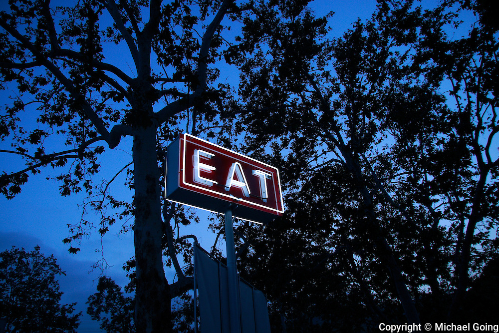 Neon Eat sign at twilight among trees