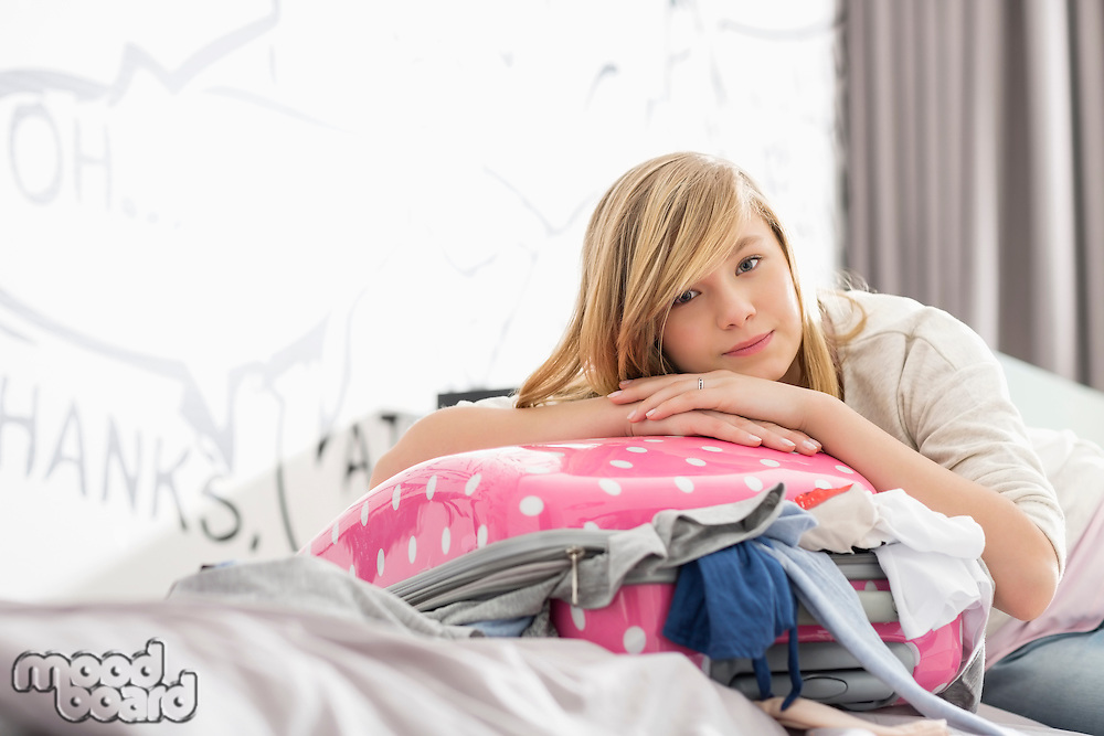 Portrait of girl relaxing on bulging suitcase at home