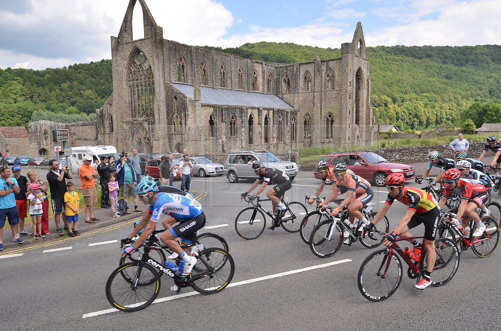 © Licensed to London News Pictures. 20/06/2014. Tintern Abbey, Chepstow, UK. Cycling: British National Road Race Championship. The main bunch screams past Tintern Abbey just over 1 minute behind a leading break including 3 from Team Sky Photo credit : Ian Homer/LNP