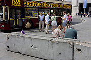 Tourists in front of a London sightseeing tour bus and others sitting on a dystopian concrete barrier.