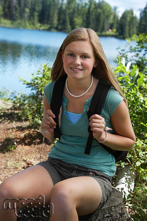 USA, Alaska, teenage girl wearing backpack at lake, portrait