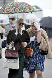 © Licensed to London News Pictures. 17/09/2011. GOODWOOD, UK. A couple shelter from a shower. The Goodwood Revival at Goodwood in West Sussex today (17 September 2011). The revival is the world's largest historic motor race meeting, which relieves the 'glorious' days of the race circuit. Competitors and enthusiasts all dress in period fashion to enhance the experience. Photo credit : Stephen Simpson/LNP