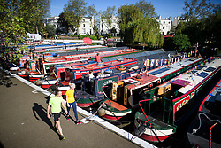 © Licensed to London News Pictures. 05/05/2018. London, UK. Walkers make their way along the canal towpath during the Canalway Cavalcade festival in Little Venice, West London on Saturday,  May 5th 2018. Inland Waterways Association's annual gathering of canal boats brings around 130 decorated boats together in Little Venice's canals on May bank holiday weekend. Photo credit: Ben Cawthra/LNP