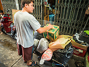 18 SEPTEMBER 2015 - BANGKOK, THAILAND: BOONLEART WANAKEE, 40, who is being evicted from his home near Wat Kalayanamit packs his belongings onto a cart. Fiftyfour homes around Wat Kalayanamit, a historic Buddhist temple on the Chao Phraya River in the Thonburi section of Bangkok, are being razed and the residents evicted to make way for new development at the temple. The abbot of the temple said he was evicting the residents, who have lived on the temple grounds for generations, because their homes are unsafe and because he wants to improve the temple grounds. The evictions are a part of a Bangkok trend, especially along the Chao Phraya River and BTS light rail lines. Low income people are being evicted from their long time homes to make way for urban renewal.             PHOTO BY JACK KURTZ