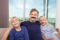 Portrait of happy father and children with artificial mustache sitting on sofa at home