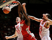 New Mexico guard Tony Snell, center, dunks the ball as Utah center David Foster, left and Utah forward J.J. O'Brien, right, defend during the second half of an NCAA college basketball game, Wednesday, Jan. 19, 2011, in Salt Lake City, Utah. Utah defeated New Mexico 82-72. (AP Photo/Colin E Braley)