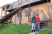 """Nina, 17 and Gigi, 11, pictured in front of the abandoned building next to their home in Vine City. """"It makes me sad and it makes the community look bad,"""" said Nina who wants to be a registered nurse or a surgeon when she grows up. """"I wish they would get some of the dope dealers off the street and get the homeless somewhere to live."""""""