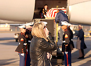 Amanda Jordan awaits the arrival of the flag-draped casket of her deceased husband, U.S. Marine Gunnery Sgt. Philip Andrew Jordan, at Bradley International Airport in Windsor Locks, Conn., Monday, March 31, 2003. Jordan, 42, was one of the first U.S. servicemen killed in action in An Nasariyah, Iraq, on March 23, 2003, while performing his duties in the 1st Battalion, 2nd Marines and 2nd Marine Division based in Camp Lejeune, NC. Jordan's burial service included full Marine honors on April 2, 2003.