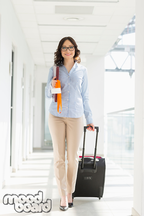 Portrait of confident businesswoman with luggage at airport