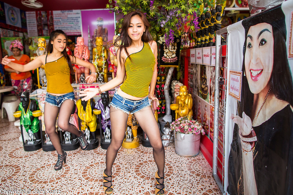 "03 MARCH 2013 - BANGKOK, THAILAND:  NAM (left) and KWANT, (stage names) ""coyote dancers"" from the Never Die dance troupe, perform for Chuchok. The Chuchok Shrine is in suburban Bangkok. More than 100 people a week come to the shrine to pray for good fortune or good health. People whose prayers are answered return to the shrine with ""coyote dancers"" to make merit and thank Chuchok. Coyote dancing is a Thai phenomenon created after the US movie ""Coyote Ugly"" where attractive young women dance in a sexually suggestive way, usually for pay. They're common at bars and festivals. Coyote dancers are typically better paid than other Thai women in the hospitality industry and usually are not allowed to date or see customers are off the dance floor. Coyote dancers perform at the Chuchok shrine because according to Buddhist literature Chuchok was a relatively repulsive old hermit and Brahmin priest who was cared for by a young woman after he made her family's wishes come true.  PHOTO BY JACK KURTZ"