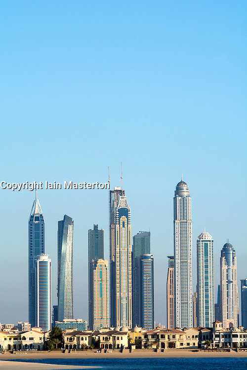 Skyline of Dubai contrasting luxury villas on The Palm Island and high-rise apartment towers at Marina area in United Arab Emirates