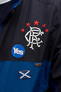 A man with a 'Yes' sticker on a Rangers Football Club jacket waiting on the Royal Mile for the start of a pro-Independence march and rally in the Scottish capital. The event, which was staged in support of the pro-Independence movement, was attended by an estimated by approximately 30,000 people. The referendum to decide whether Scotland will become an independent nation will be staged on 18th September 2014.