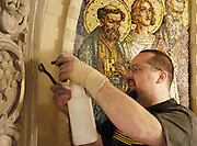 Kevin Joyner uses a wire brush and a bottle of water to remove stains built up over the years on the decorative stone arch in the sanctuary of the national shrine of Mary Help of Christians. Feb. 24. (Catholic Herald photo by Sam Lucero)