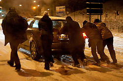 Good sanitarians help pushing a car up the A629 Cowley Hill towards Junction 35 M1 from Chapeltown Sheffield..30th November 2010.Images © Paul David Drabble