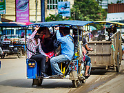 05 JULY 2017 - POIPET, CAMBODIA:  Cambodian migrant workers in Poipet headed for Thailand take a tuk-tuk (three wheeled taxi) to the Thai-Cambodian border. The Thai government proposed new rules for foreign workers recently. The new rules include fines of between 400,000 and 800,00 Thai Baht ($12,000 - $24,000 US) and jail sentences of up to five years for illegal workers and people who hire illegal workers. Hundreds of companies fired their Cambodian and Burmese workers and tens of thousands of workers left Thailand to return to their countries of origin. Employers and human rights activists complained about the severity of the punishment and sudden implementation of the rules. On Tuesday, 4 July, the Thai government suspended the new rules for 180 days and the Cambodian and Myanmar governments urged their citizens to stay in Thailand, but the exodus of workers continued through Wednesday.    PHOTO BY JACK KURTZ