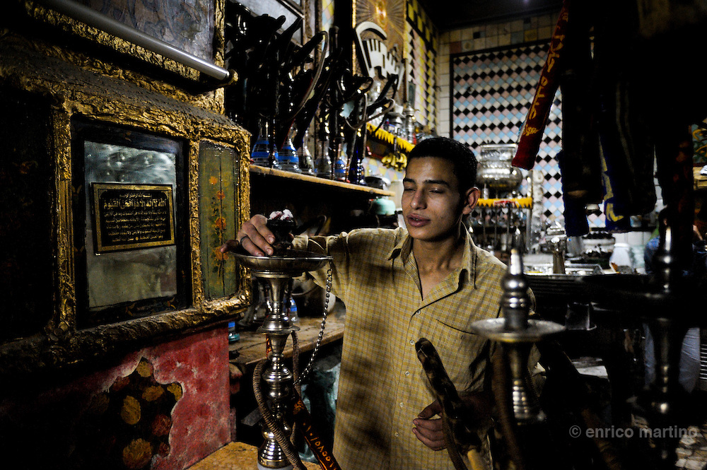 El Shems, a traditional tea and coffee house (ahwa) with his incredible kitsch furnishing. A waiter preparing shesha (water pipes). Cairo's ahwa (the traditional coffeehouse) are for Cairo what the pub is to London or caffè to Rome. Once the ahwa was the main place for entairnement, a animated place where Cairo's men socialised playing chess, backgammon or domino, reading newspapers or watching TV, drinking Turkish coffee and shai (tea) with mint or smoking a sheesha, the tradional waterpipe. Some ahwa are meeting places for people loving chess or remembering famous Egyptian singer Oum Kalthoum. Today Cairo is changed and everybody is just too busy to drink coffee in a ahwa, so western style coffee shops are much more than traditional ahwa.