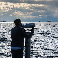 A man looks through a binocular on the seafront of Trieste, Italy.