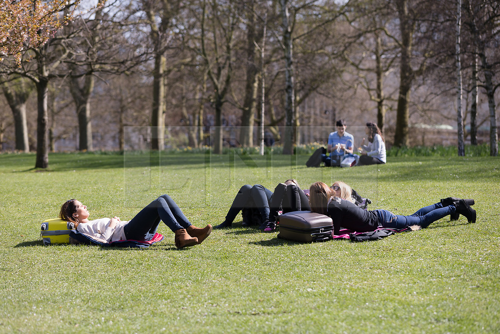 © Licensed to London News Pictures. 26/03/2017. LONDON, UK. Tourists with suitcases relax during sunny spring weather in St James's Park, London this lunchtime. Today is the first day of British Summer Time (BST). Photo credit: Vickie Flores/LNP