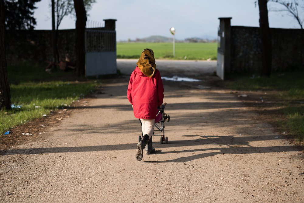 A refugee girl pushing a pram at the disused Centre of Sanitary Veterinary Control of Idomeni. <br /> <br /> Thousands of refugees are stranded in Idomeni unable to cross the border. The facilities are stretched to the limit and the conditions are appalling.