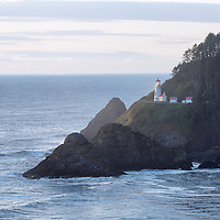 Heceta Head Lighthouse flashes out its warning of the dangers of the rocks below. Near Florence, Oregon.