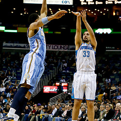 Mar 25, 2013; New Orleans, LA, USA; New Orleans Hornets power forward Ryan Anderson (33) shoots over Denver Nuggets center JaVale McGee (34) during the first quarter of a game at the New Orleans Arena. Mandatory Credit: Derick E. Hingle-USA TODAY Sports