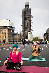 © Licensed to London News Pictures. 07/10/2019. London, UK. Climate change activists do yoga on Westminster Bridge, London, during a sit down demonstration closing the entire bridge to traffic, as part of a wider two week long demonstration to cause disruption in the capital. The activists are calling for the government to acknowledge and act on climate change. Photo credit : Tom Nicholson/LNP