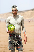 Water Melon fruit seller portrait, Rmilate / Paradise Beach, Asilah, Morocco, 2015-08-09.<br /><br />Many locals and tourists get a free exfoliation using a natural clay rock deposit found inside the cliffs at the Northern end of the beach. <br /><br />Paradise may be somewhat of an over statement, but the beach 2km south of Asilah is worth a visit. <br /><br />Collective taxis run back and forth throughout the day from nearby the Banque Populaire in the centre of Asilah and return back to town from the beach around sunset. <br /><br />Sharing a collective taxi is an interesting adventure in itself, as you pass by unspoilt areas of Morocco's rugged coastline. <br /><br />Known locally as 'Rmilate', the beach is packed full of tourists during the summer months and is best visited off season, when you can expect to have a large space to yourself. <br /><br />Numerous cabin hut restaurants line the base of the cliffs enclosing the beach, serving up freshly grilled sardines, moroccan salads and fish tagines.<br /><br />This beach is much more clean and wild than the main beach strip adjacent to the main town of Asilah. It's worth taking the short collective taxi ride out to this beach when seeking a day out by the seaside rather than camping on the main Asilah beach.