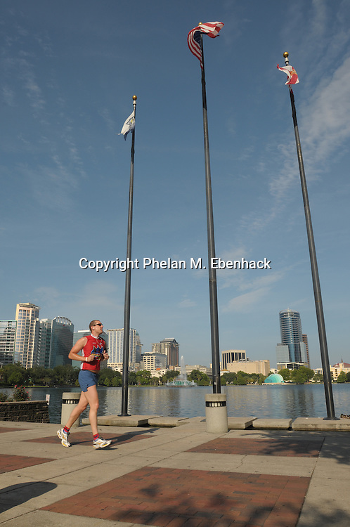 A man runs past and stand of flags at Lake Eola Park in downtown Orlando, Florida.